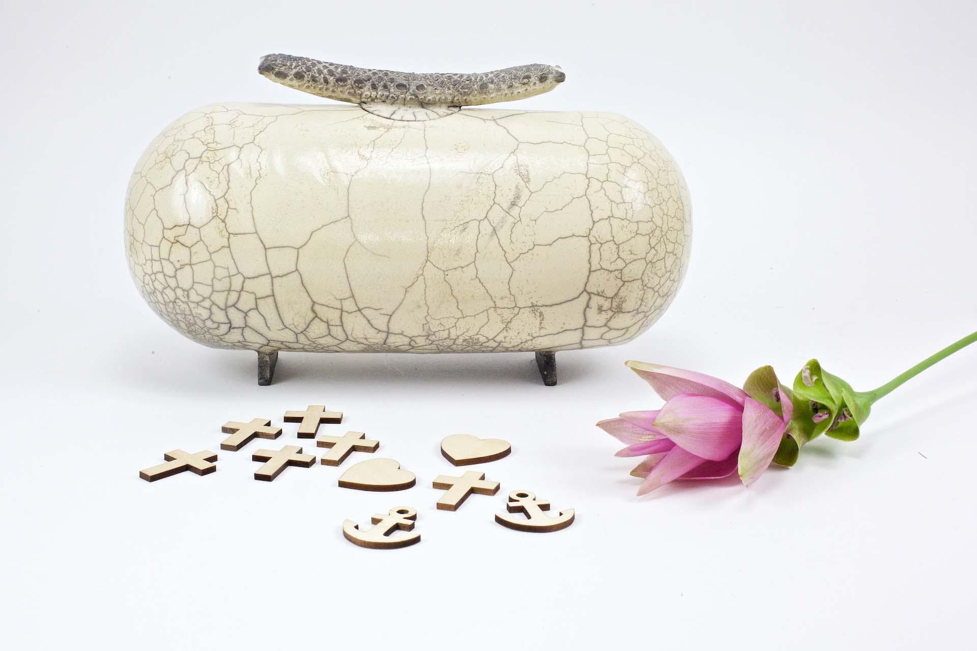 witte keramieken urn van marieke vergouw met deksel en houten kruisjes, hartjes en ankertjes van monumentaalste en een rosé bloem uitvaart1001lichtjes inspiratie