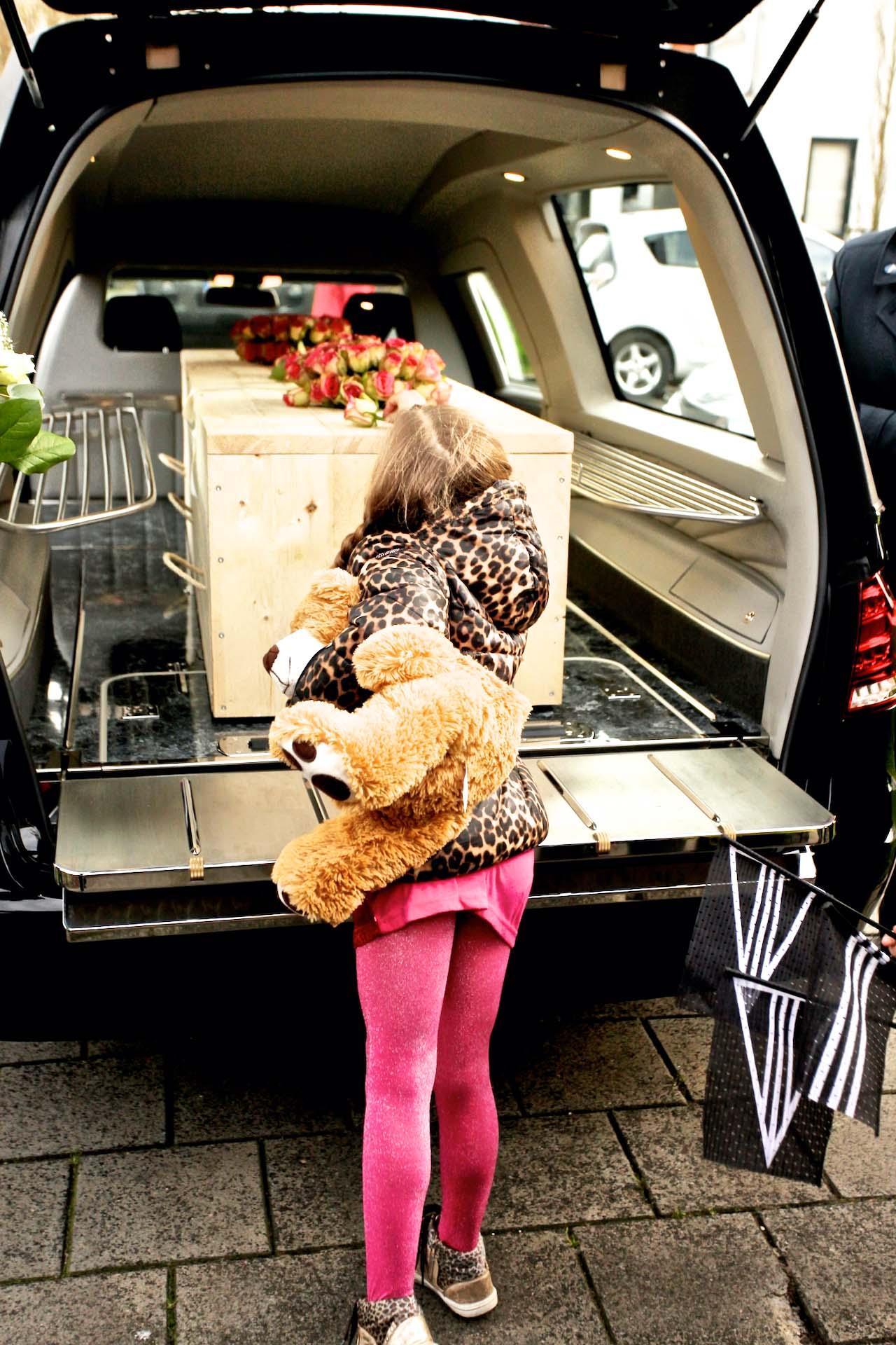 uitvaartkist in auto op weg naar de eindbestemming met klein meisje ervoor die een laatste bloem op de kist legt uitvaart1001lichtjes inspiratie afscheid rouwauto